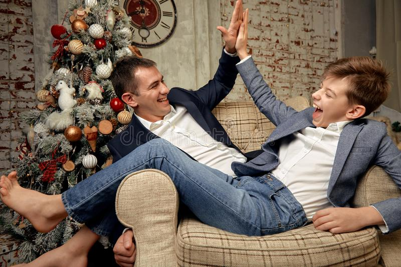 Son and father rejoice against the backdrop of Christmas decorations. The son and father are sitting in a chair and. Joyfully chatting on Christmas Eve royalty free stock images