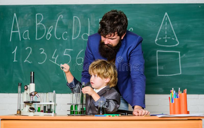 Son and father at school. small boy with teacher man. Wisdom. Back to school. Pharmacy and chemistry theme. solution in royalty free stock photos