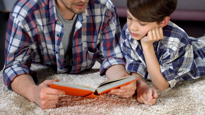 Son and father spending time together reading interesting book, divorced parents stock photo