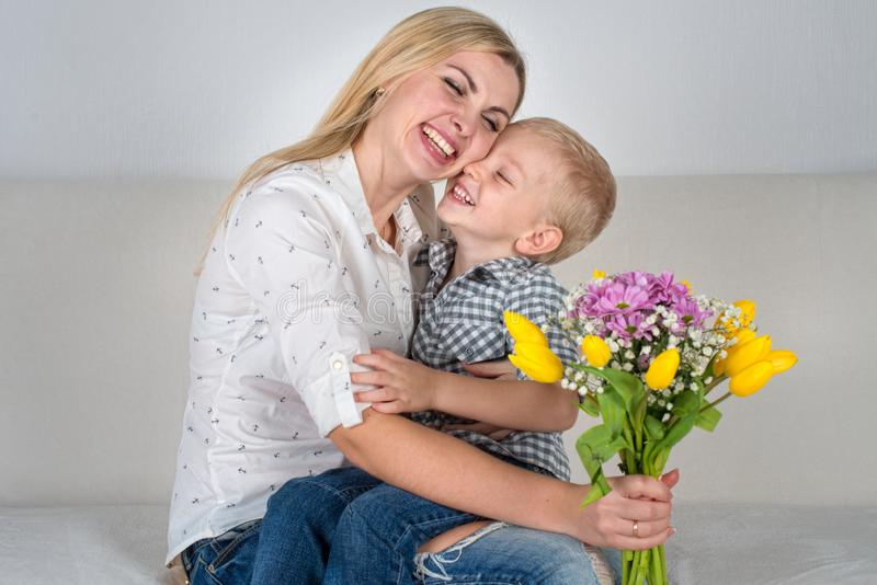 Son gives his beloved mother a beautiful bouquet of tulips.The concept of the celebration,women`s day. The concept of the celebration,women`s day.Son gives his stock image