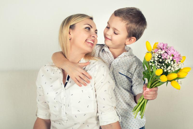 Son gives his beloved mother a beautiful bouquet of tulips.The concept of the celebration,women`s day. stock photo