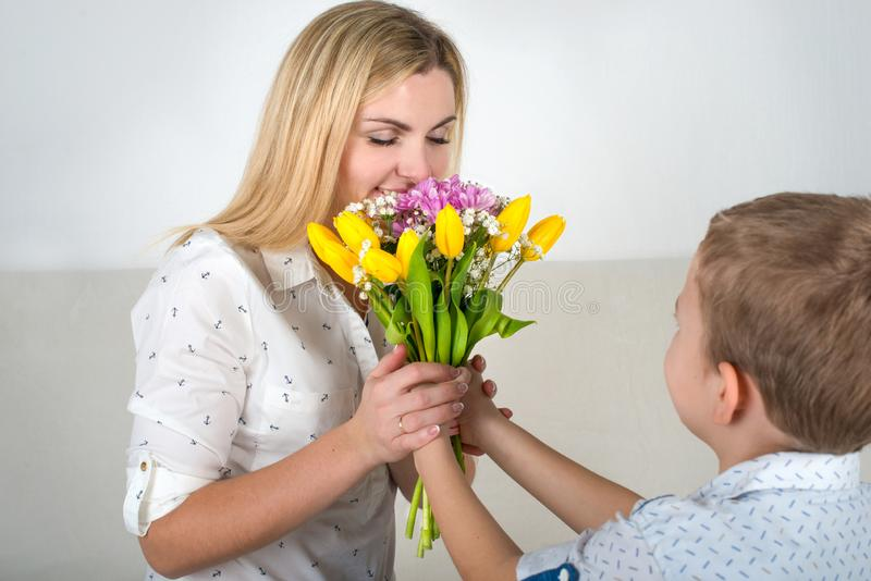 Son gives his beloved mother a beautiful bouquet of tulips.The concept of the celebration,women`s day. royalty free stock images