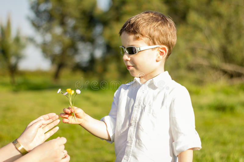 Son giving a bouquet of flowers to his mother in a field stock photo