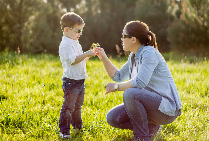 Son giving a bouquet of flowers to his mother in a field stock images