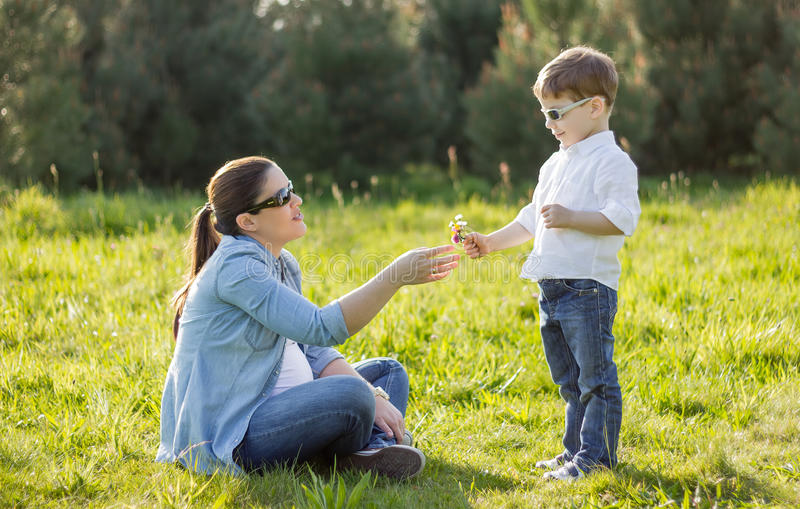 Son giving a bouquet of flowers to his pregnant mother in a field stock photography