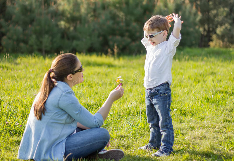 Son giving a bouquet of flowers to his pregnant mother in a field stock images