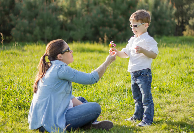 Son giving a bouquet of flowers to his pregnant mother in a field stock image
