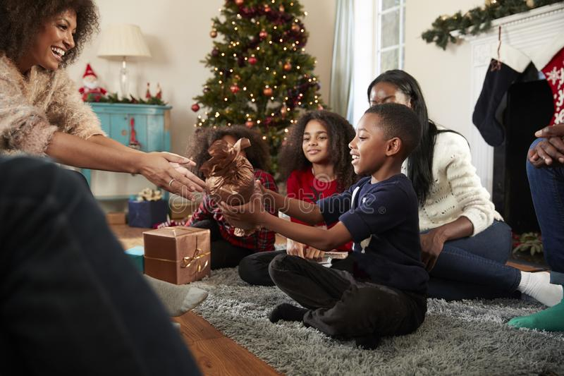 Son Giving Mother Gift As Multi Generation Family Celebrate Christmas At Home Together royalty free stock photos