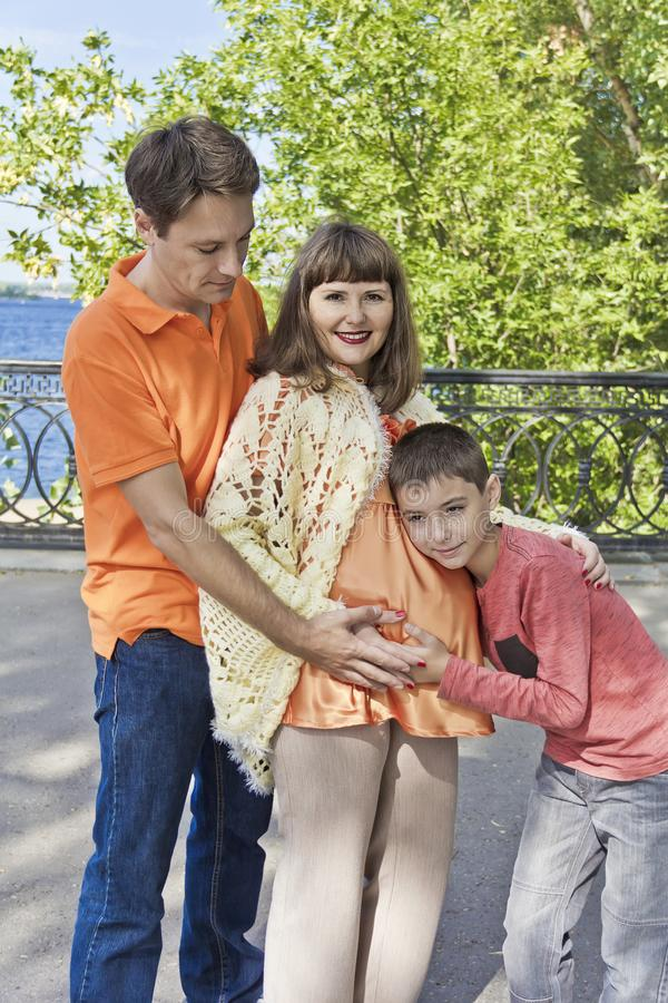 Son is hearing stomach of pregnant mother with father stock image