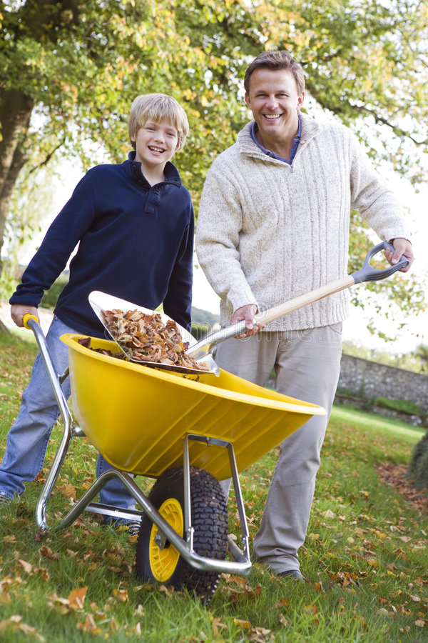 Son helping father to collect leaves stock photo
