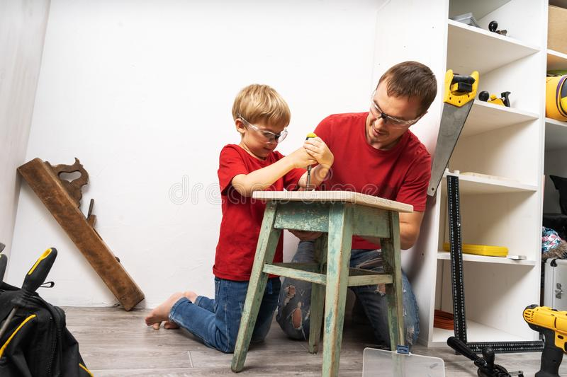 The son helps his father around the house with male work. Screws a screw into an old stool with a screwdriver. Family lifestyle portrait royalty free stock images