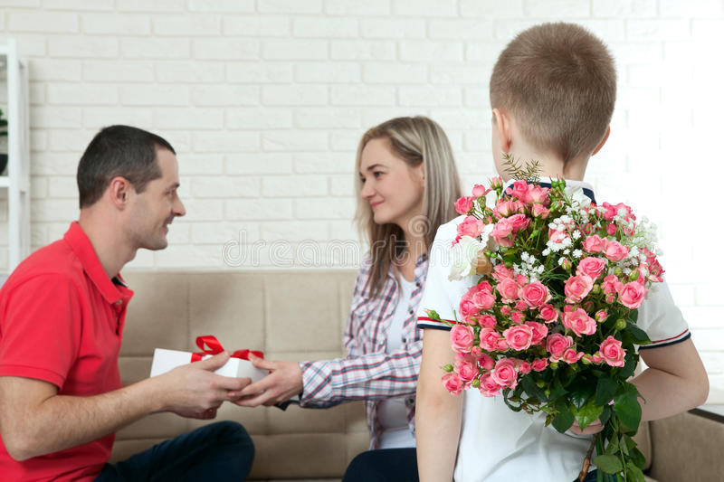 Son hiding bouquet to surprise mommy on mother`s day. Woman, man royalty free stock images