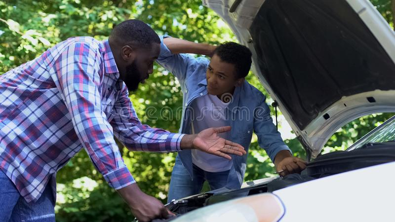 Son hitting upside head while father scolding, repairing car together upbringing royalty free stock photography
