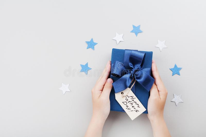 Son holding a gift or present box with Happy fathers day tag. Holiday concept top view. Son holding a gift or present box with Happy fathers day tag. Holiday stock images