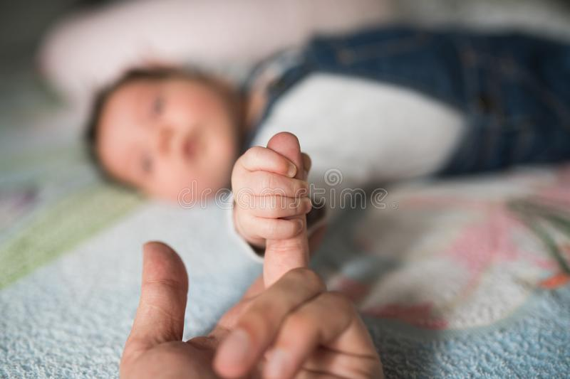 Son holds father by the hand. close-up. Closeup of a senior man and girl holding hands stock images