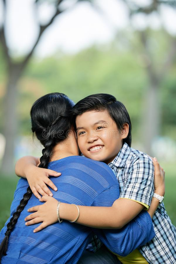 Son hugging mother. Outdoor portrait of smiling cheerful Asian boy hugging his mother to express love royalty free stock images