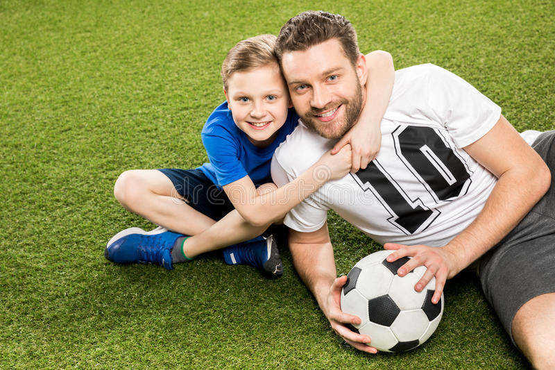 Son hugging smiling father while lying on grass. Happy son hugging smiling father while lying on grass royalty free stock photo