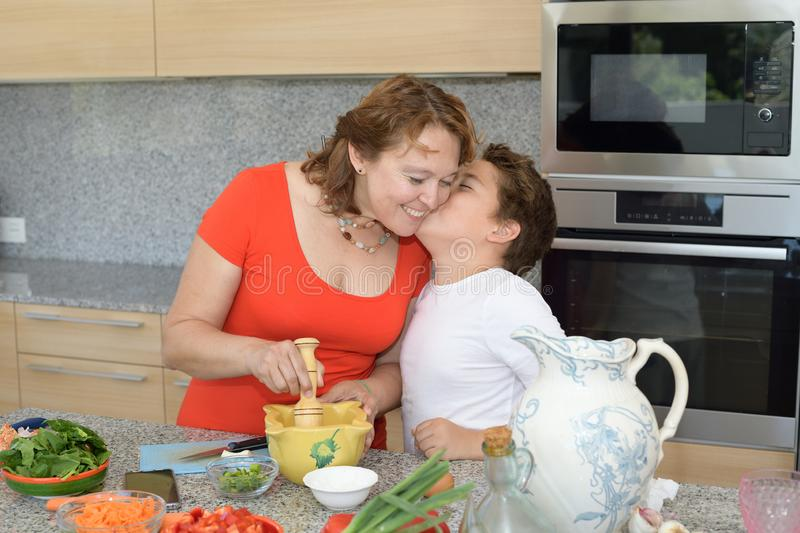 Son kisses his mother while they prepare lunch stock photo
