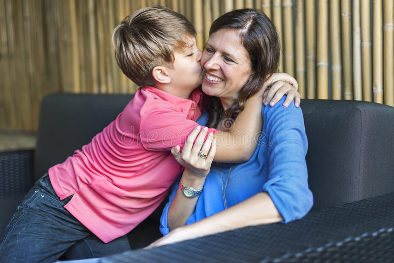 Son Kissing Mother Hugging Family Concept stock photo