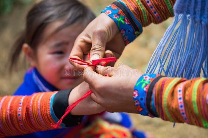 Son La Vietnam - Januari 13, 2016: Etniska barn för H-`-mong i traditionell kläder som spelar en lek vid plötsligt, binder upp fi royaltyfria bilder