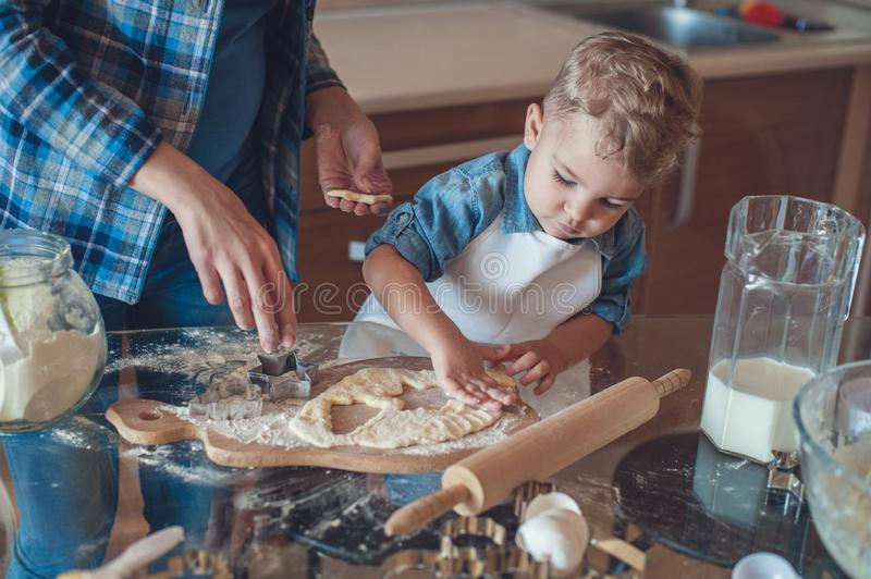Son making cookies. With dough molds royalty free stock image