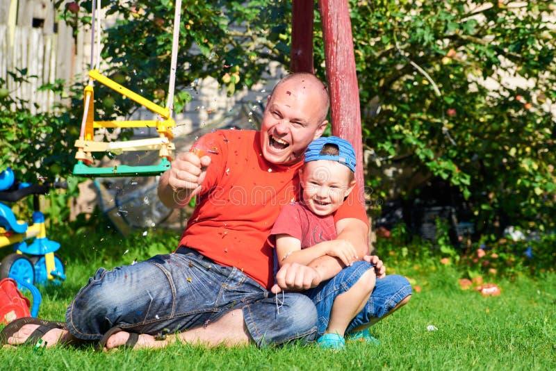 Son med hans fader blåste pappers- smällare royaltyfri foto