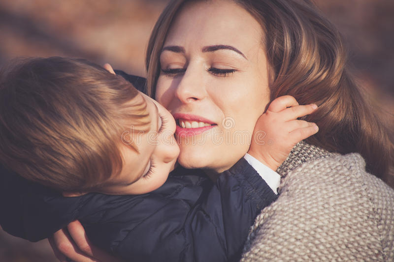 Son and mom in hug stock photo