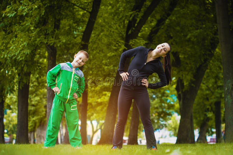 Son and mother are doing exercises in the park royalty free stock photography