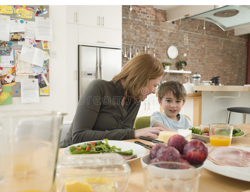 Son And Mother Having Meal At Dining Table In Kitchen. Portrait of son and mother having meal together at dining table in kitchen royalty free stock photography