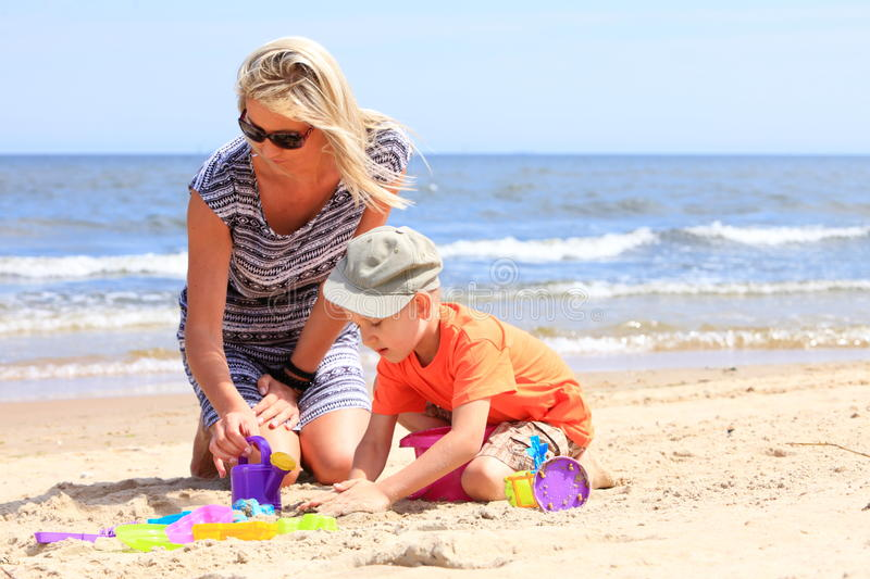 Son and mother playing toys on beach royalty free stock image