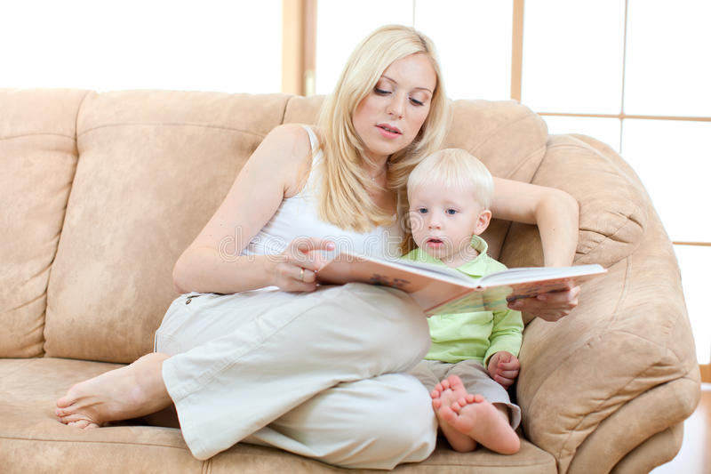Son and mother sitting on sofa and reading book stock photography