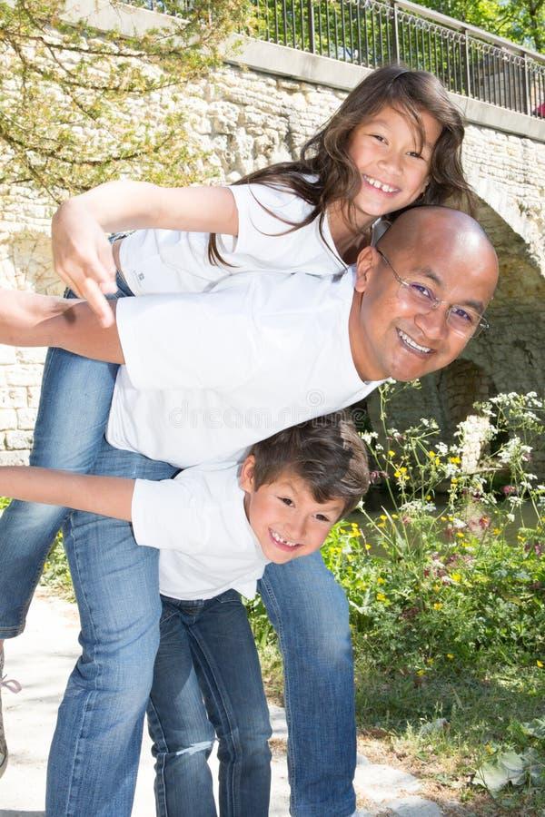 Son och dotter för ton för faderGiving Children Piggyback ritt utomhus royaltyfri bild