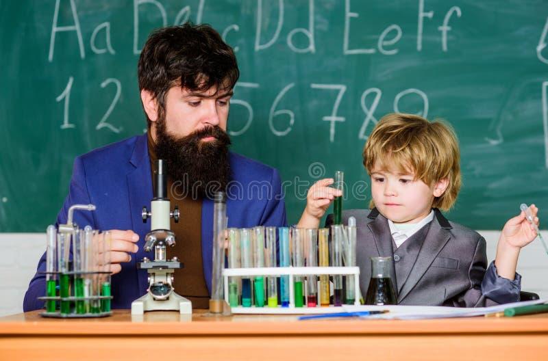 Son och fader på skola liten pojke med läraremannen utbildande rum med svart tavla Flaska i forskarehand med provet royaltyfri fotografi