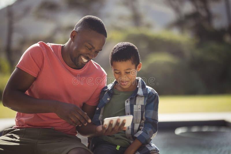 Son och fader som använder mobiltelefonen nära poolside royaltyfria foton