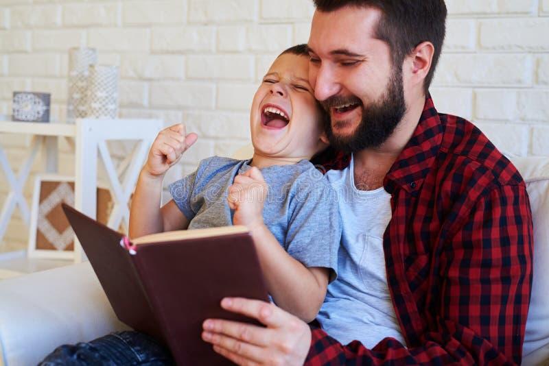 Son och farsa som skrattar och läser en bok arkivbilder