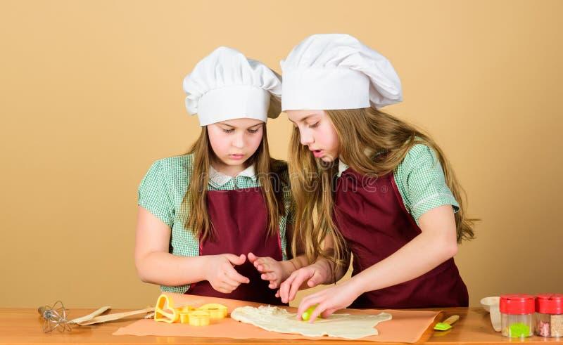 Son pas les dieux qui font des pots cuire au four Petits enfants roulant la pâte pour faire des tartes cuire au four Les petites photo libre de droits