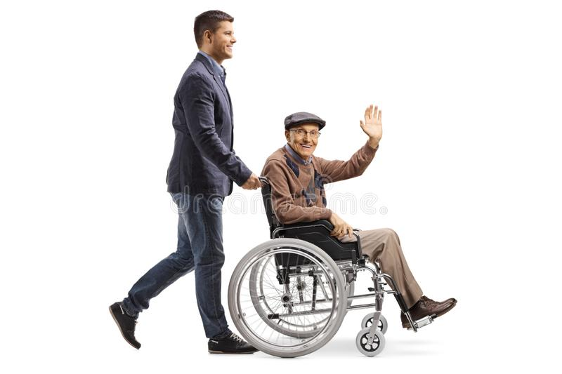 Son pushing his father waving from a wheelchair royalty free stock image