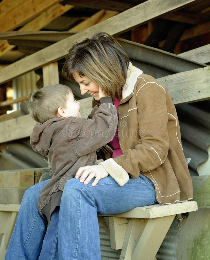 Happy Couple Sitting On Sandy Beach Embracing Kissing: Mother And Child Cuddling Sitting On Bench Stock Image