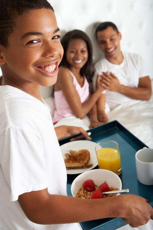 Son som kommer med föräldrar frukosten i säng arkivbilder
