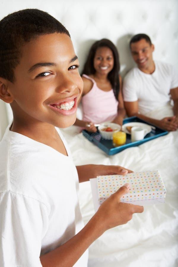 Son som kommer med föräldrar frukosten i säng arkivbild