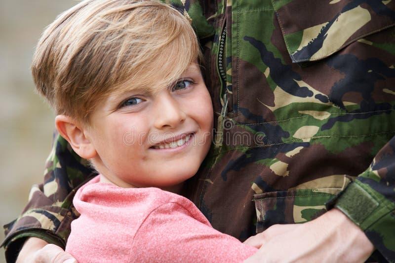 Son som kramar den militära fadern Home On Leave royaltyfri foto