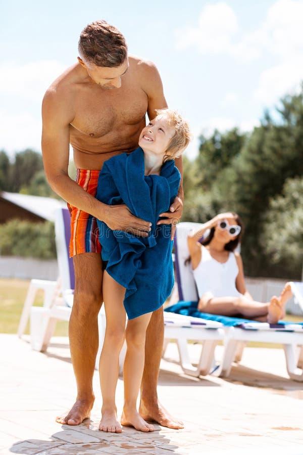 Son som ser pappakänsla som är tacksam, når att ha simmat i pöl royaltyfria bilder