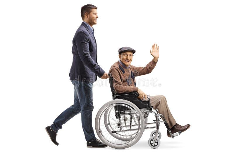 Son som skjuter hans fader som vinkar fr?n en rullstol royaltyfri bild