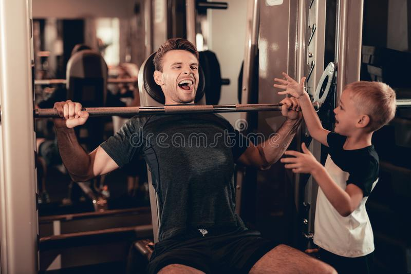 Son Support To Father While Lifting The Barbell. royalty free stock photos