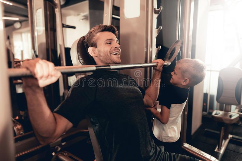 Son Support To Father While Lifting The Barbell. stock photos