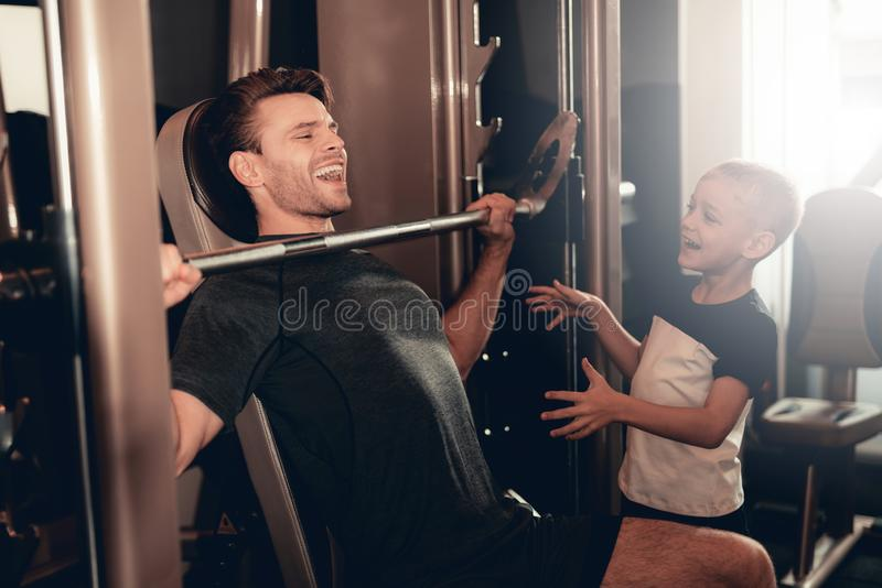 Son Support To Father While Lifting The Barbell. stock photography