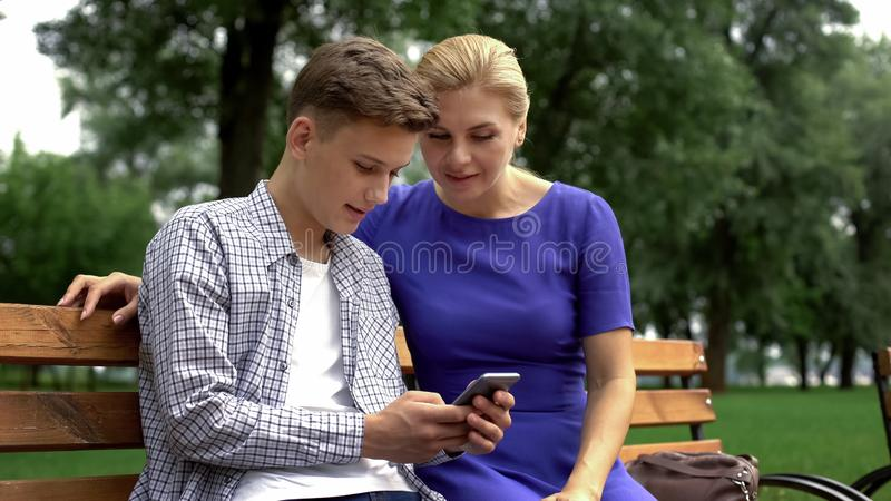 Son teaching mother to use application on smartphone, new technologies, gadget. Stock photo royalty free stock photography