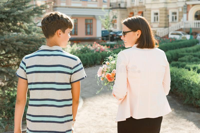 Son is teenager walking with his mother outdoor, mom holding bouquet of flowers gift from her son on mother`s day, view from the stock photo