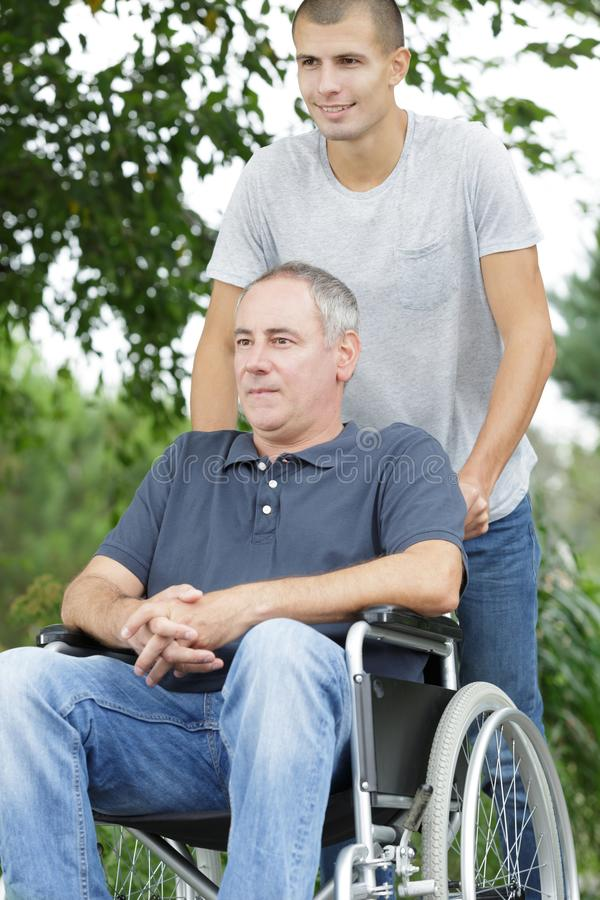Son walking with disabled father in wheelchair at park royalty free stock photos