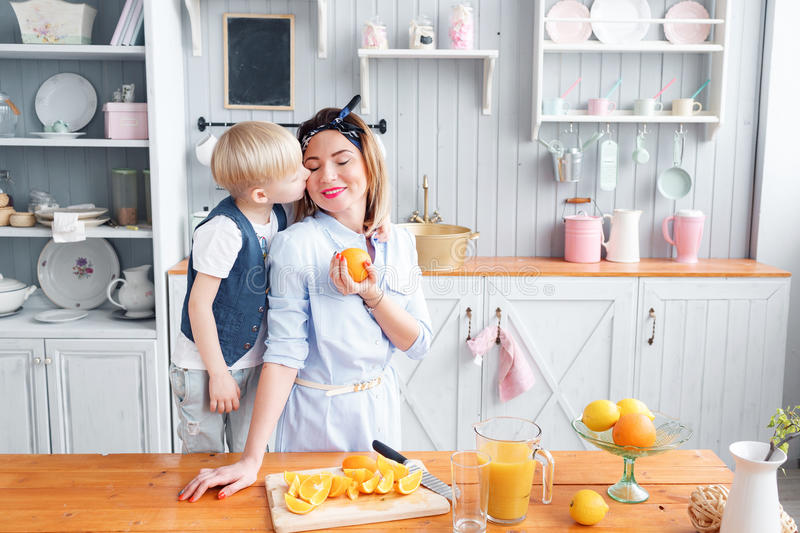 Son and young mother in the kitchen eating Breakfast. Mom cuts fruit to her son. sliced oranges on a wooden cutting board. Healthy and tasty breakfast stock photos